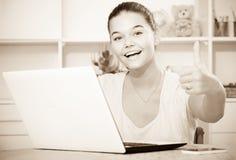 Alumno de la escuela de la muchacha que se sienta con el ordenador portátil y que muestra los pulgares para arriba Fotos de archivo libres de regalías
