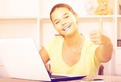Alumno de la escuela de la muchacha que se sienta con el ordenador portátil y que muestra los pulgares para arriba Fotografía de archivo libre de regalías