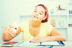 Alumno de la escuela de la muchacha que toma el autorretrato en smartphone mientras que estudio Imagen de archivo libre de regalías