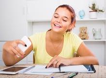 Alumno de la escuela de la muchacha que toma el autorretrato en smartphone mientras que estudio Foto de archivo libre de regalías