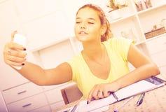 Alumno de la escuela de la muchacha que toma el autorretrato en smartphone mientras que estudio Imagenes de archivo
