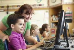 Alumno de la escuela primaria con el profesor In Computer Class Imagen de archivo