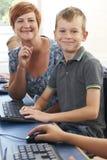 Alumno elemental masculino en clase del ordenador con el profesor imágenes de archivo libres de regalías