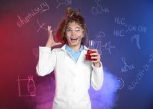 Alumno emocional que sostiene el frasco cónico contra la pizarra con fórmulas de la química imagen de archivo
