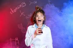 Alumno emocional que sostiene el frasco cónico en humo con fórmulas de la química fotografía de archivo