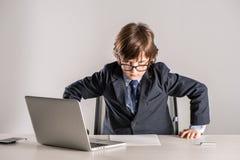 Alumno en el traje de negocios que se coloca sobre el escritorio Foto de archivo libre de regalías