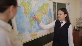 Alumno en el uniforme escolar que se coloca cerca de un mapa del mundo durante una lección de la geografía almacen de video