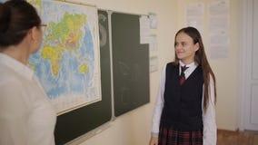 Alumno en el uniforme escolar que se coloca cerca de un mapa del mundo durante una lección de la geografía almacen de metraje de vídeo