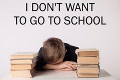 Alumno en traje en su escritorio en fondo gris con los libros El muchacho se cayó dormido durante la preparación ` De la inscripc Imagen de archivo libre de regalías