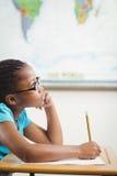 Alumno enfocado que trabaja en su escritorio en una sala de clase foto de archivo libre de regalías