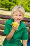 Alumno feliz lindo que come el mollete hecho en casa al aire libre fotografía de archivo libre de regalías