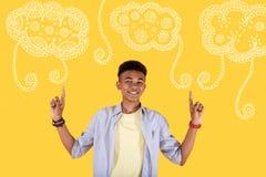 Alumno feliz que destaca sus fingeres y que muestra nuevo diseño en su sala de clase Foto de archivo