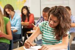 Alumno femenino que estudia en el escritorio en sala de clase Fotografía de archivo libre de regalías