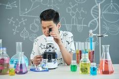 Alumno hermoso que usa el microscopio Imagenes de archivo