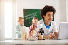 Alumno joven agradable que usa un ordenador portátil Foto de archivo