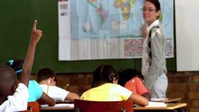 Alumno joven que aumenta la mano durante la lección de la geografía en sala de clase metrajes
