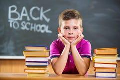 Alumno lindo con los libros en sala de clase Foto de archivo