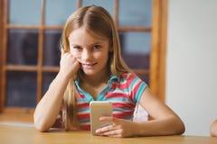 Alumno lindo en clase usando smartphone Imagen de archivo libre de regalías