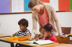 Alumno lindo que consigue ayuda de profesor en sala de clase Imágenes de archivo libres de regalías
