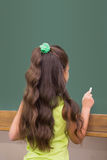 Alumno lindo que se coloca en la escritura de la sala de clase en la pizarra Imagen de archivo libre de regalías