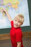 Alumno lindo que sonríe en la cámara en la sala de clase que señala al mapa Foto de archivo libre de regalías