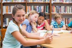 Alumno lindo que usa la tableta en biblioteca Imagen de archivo