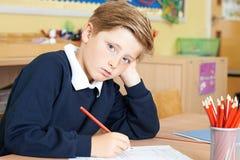 Alumno masculino agujereado de la escuela primaria en el escritorio imagenes de archivo