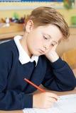 Alumno masculino agujereado de la escuela primaria en el escritorio imágenes de archivo libres de regalías