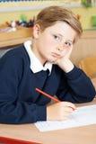 Alumno masculino agujereado de la escuela primaria en el escritorio Fotografía de archivo