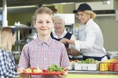 Alumno masculino con el almuerzo sano en cafetería de la escuela Fotos de archivo