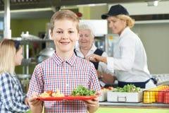 Alumno masculino con el almuerzo sano en cantina de la escuela imagen de archivo