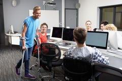 Alumno masculino que camina en las muletas en clase del ordenador Imágenes de archivo libres de regalías
