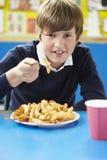 Alumno masculino que come el almuerzo escolar malsano fotografía de archivo