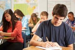 Alumno masculino que estudia en el escritorio en sala de clase Imágenes de archivo libres de regalías