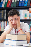 Alumno masculino subrayado que trabaja en biblioteca Imagenes de archivo