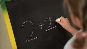 Alumno que practica matemáticas simple en el tablero de tiza almacen de video