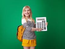Alumno que señala en igualmente dominante en la calculadora en fondo verde fotografía de archivo libre de regalías