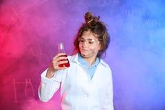 Alumno que sostiene el frasco cónico en humo contra la pizarra con fórmulas de la química imagen de archivo
