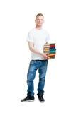 Alumno que sostiene una pila de libros aislados en blanco Foto de archivo libre de regalías
