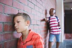 Alumno que tiraniza a un muchacho triste en pasillo Imagen de archivo libre de regalías