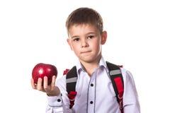 Alumno sano con la mochila que sostiene una manzana roja, en el fondo blanco, macro Fotografía de archivo