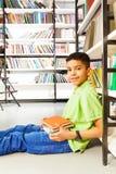 Alumno sonriente con la pila de libros que se sientan en piso Imagen de archivo libre de regalías
