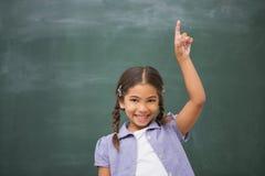Alumno sonriente que aumenta su mano imagenes de archivo