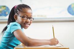 Alumno sonriente que trabaja en su escritorio en una sala de clase Imagen de archivo