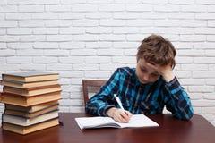 Alumno subrayado y agotado con los papeles rasgados que se sientan en el DES Imagenes de archivo
