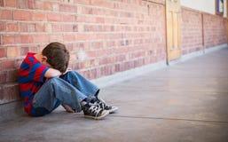 Alumno triste que se sienta solamente en pasillo Imagenes de archivo