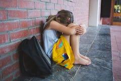 Alumno triste que se sienta solamente en pasillo Fotografía de archivo libre de regalías