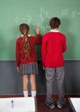 Alumnos adolescentes que escriben a bordo Fotografía de archivo
