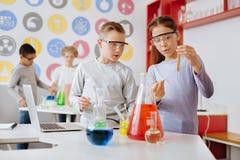 Alumnos agradables que examinan el tubo de ensayo con la sustancia química Imágenes de archivo libres de regalías