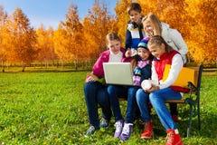 Alumnos con el ordenador en parque Fotografía de archivo libre de regalías